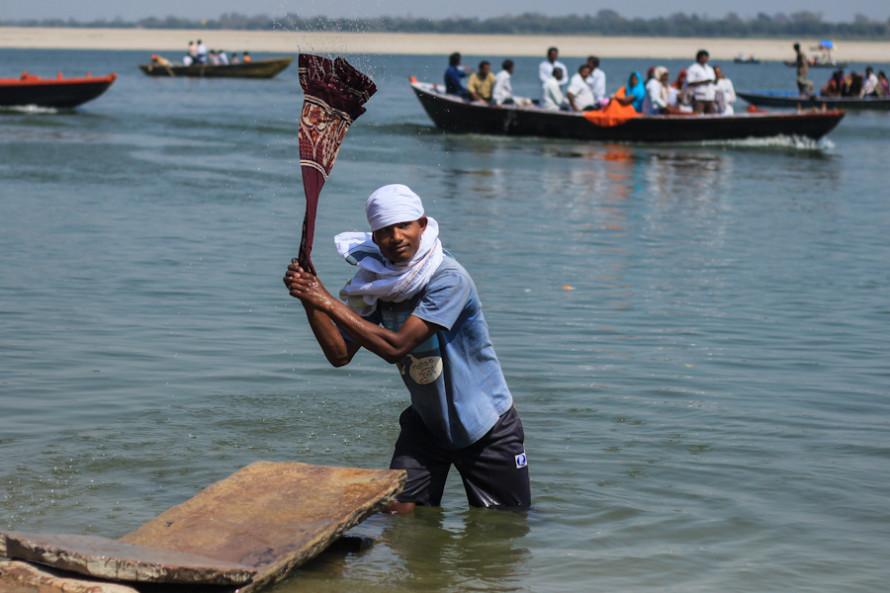 Hombres y mujeres se dedican a la var la ropa en el Ganges.
