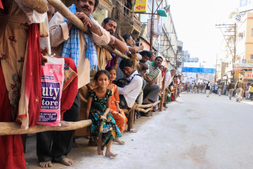 Los civiles esperan su paso desde atrás de un vallado.