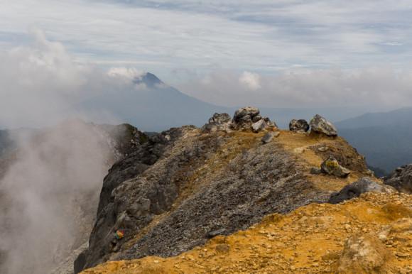 Desde arriba de una de las paredes del cráter se ve, entre las nubes, el otro volcán.