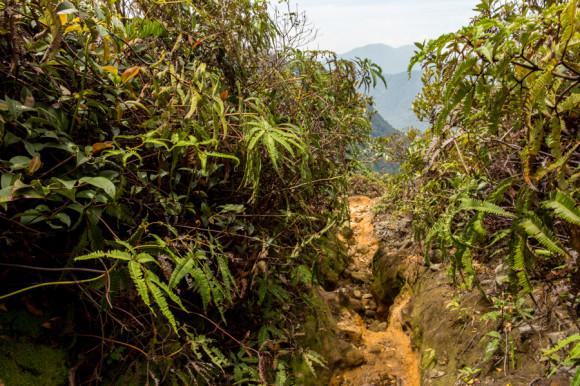 La vueta hacia Semangat Gunung Village empieza por un sendero entre verde y rocoso.